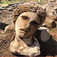 Chiếc đầu cẩm thạch hiện ra trên bức tường phế tích