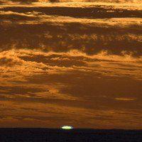 Mặt Trời lặn tỏa ánh sáng xanh lá trên biển